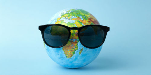 Tourism, ecology, vacation and globalism concept. Globe in sunglasses on a blue background banner. Minimal creative.